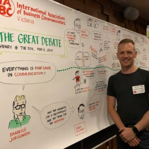 Matthew Magain stands next to his capture of the IABC Victoria Great Debate